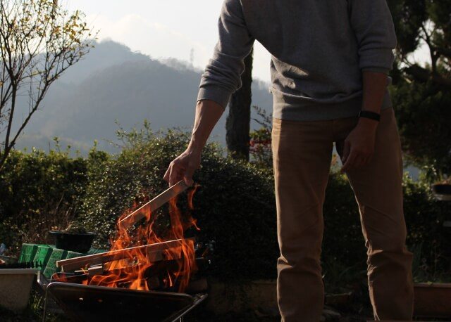 焚き火に薪をくべる